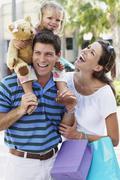 Hispanic family walking with shopping bags outdoors Stock Photos