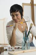 Portrait of Hispanic female artist holding paintbrush Stock Photos