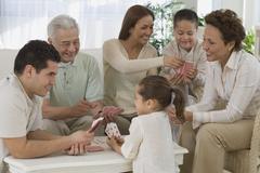 Multi-generational Hispanic family playing cards - stock photo