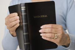 Close up of woman holding Spanish bible Stock Photos