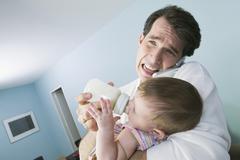 Stressed Hispanic father feeding baby Stock Photos