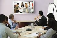 Stock Photo of Multi-ethnic businesspeople having video conference