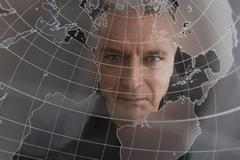 Businessman looking at clear globe Stock Photos