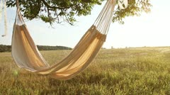 Hammock swinging on the wind at sunset - stock footage