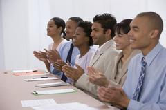 Multi-ethnic businesspeople clapping Stock Photos