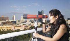 Hispanic woman looking through telescope on balcony - stock photo
