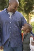 African father and son smiling at each other Stock Photos