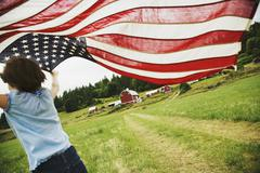 Girl running with American flag on farm - stock photo