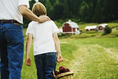 Father and son walking on farm Stock Photos
