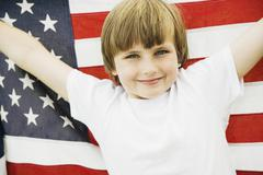 Boy holding up American flag - stock photo