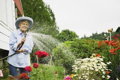 Senior woman watering plants with hose Stock Photos