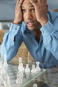 Mixed Race man playing chess - stock photo