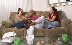 Multi-ethnic friends eating take out food Stock Photos