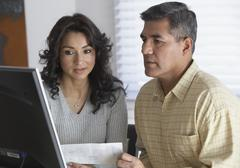 Hispanic couple looking at computer Stock Photos