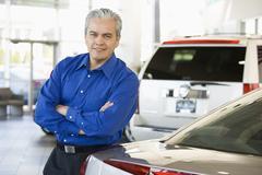 Hispanic car salesman leaning on new car Stock Photos