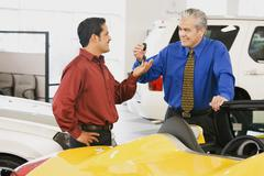Hispanic car salesman handing car keys to buyer Stock Photos