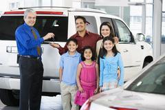 Hispanic car salesman handing car keys to family - stock photo