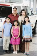 Hispanic family at car dealership - stock photo