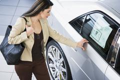 Hispanic woman looking at new car - stock photo