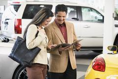 Hispanic couple at car dealership - stock photo