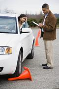 African teenager running over traffic cone at drivers test Stock Photos