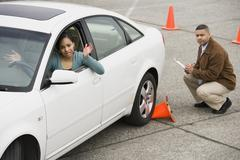 African teenager running over traffic cone at drivers test - stock photo