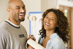 African couple being silly with paint rollers - stock photo