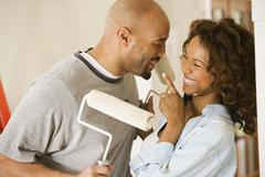 African couple being silly with paint rollers Stock Photos