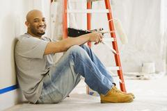 African man taking break from painting Stock Photos