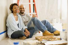African couple taking lunch break from painting - stock photo
