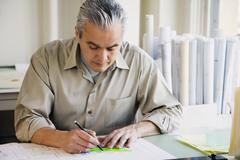 Hispanic male architect writing at desk - stock photo