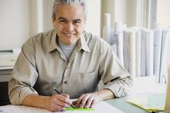 Hispanic male architect writing at desk Stock Photos