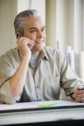 Hispanic male architect talking on cell phone - stock photo