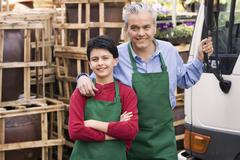 Hispanic father and son working at garden center Stock Photos
