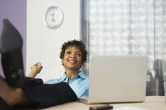 African businesswoman with feet up on desk Stock Photos