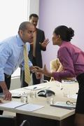 Multi-ethnic businesspeople arguing across table Stock Photos