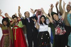 Multi-ethnic people in traditional dress cheering - stock photo