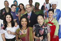 Multi-ethnic people in traditional dress holding American flags - stock photo