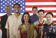 Multi-ethnic people standing in front of American flag - stock photo