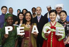 Multi-ethnic people holding the word PEACE - stock photo