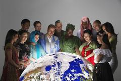 Multi-ethnic people in traditional dress looking at globe - stock photo