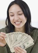 Asian woman counting money - stock photo