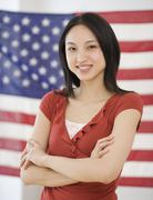 Asian woman standing in front of American flag Stock Photos