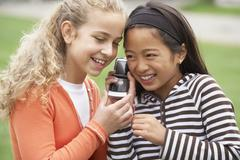 Multi-ethnic girls listening to cell phone Stock Photos