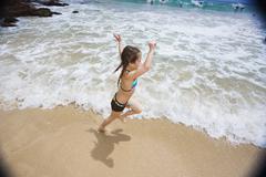 Asian girl running on beach Stock Photos