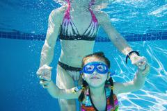 Underwater shot of Asian mother and daughter Stock Photos