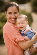 Hispanic mother holding baby - stock photo