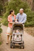 Hispanic parents pushing baby in stroller - stock photo