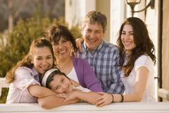 Hispanic family hugging on porch Stock Photos