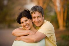 Hispanic couple hugging in park Stock Photos
